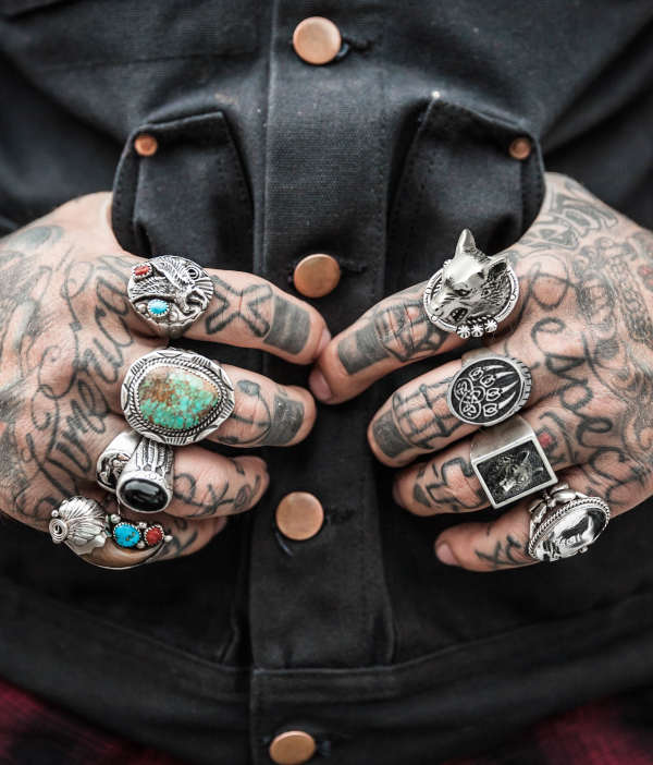 wolf ring collection showing a man tattooed hands with wolf rings